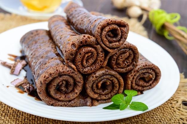 Delicate frittelle al cioccolato, arrotolate, disposte in una pila su un piatto bianco e una tazza di tisana