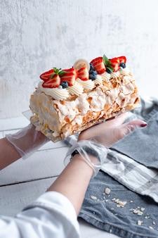 Delicato dessert meringa roll con fragole e petali di mandorle nelle mani di un pasticcere