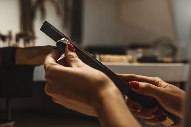 Delicato lavoro di gioielleria. primo piano delle mani di un gioielliere femminile che lavorano e modellano un anello incompiuto con uno strumento al banco di lavoro in officina. processo di creazione di gioielli. affare. laboratorio di gioielli.