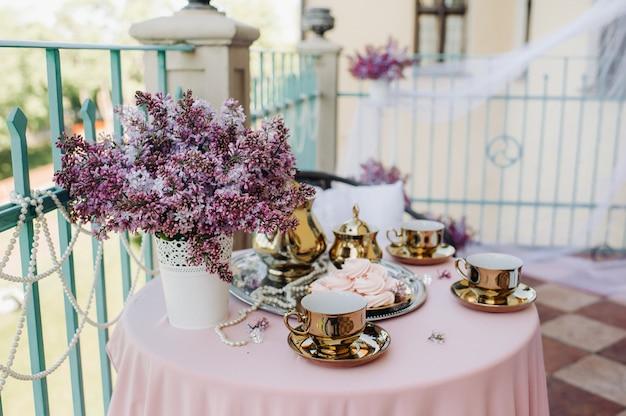 Delicato tavolo da tè mattutino con fiori lilla, antichi cucchiai e piatti su un tavolo con una tovaglia rosa.