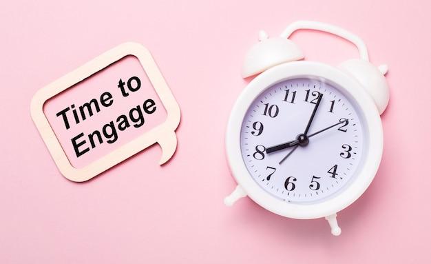 Su un delicato sfondo rosa, una sveglia bianca e una cornice di legno con la scritta time to engage
