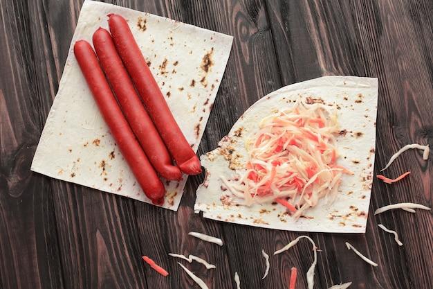Salsicce delicate, cavolo cappuccio e pane pita su fondo di legno.