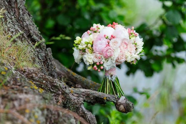 Un bouquet da sposa delicato e molto bello di rose, peonie, eustoma e idrogenazione su uno sfondo di verde. floristica della sposa nei colori rosa e bianchi. manico decorato con pizzo e chiave