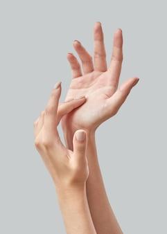 Mani di donna delicate. le mani femminili applicano crema, lozione. manicure e concetto di cura della pelle delle mani. avvicinamento