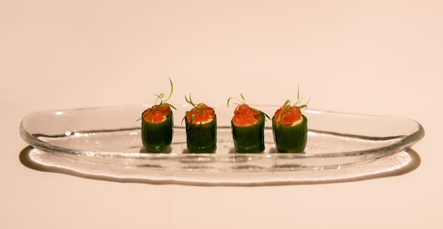 Delizioso antipasto, piccoli cetrioli ripieni di formaggio leggero e decorati con caviale di salmone rosso (messa a fuoco selettiva)