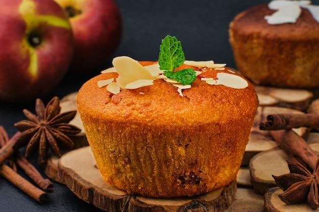 Delizioso muffin alle mele con cannella con mele e scaglie di mandorle decorate con una foglia di menta, primo piano, messa a fuoco selettiva. tea time o colazione, torte fatte in casa