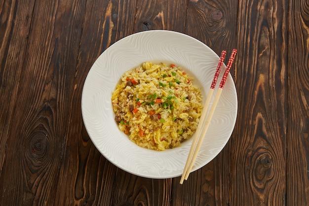 Delizioso riso fritto asiatico con carne di manzo, uova, carote, aglio e cipolla verde con vista orizzontale bacchette dall'alto sul piatto bianco tavolo in legno, spazio di copia