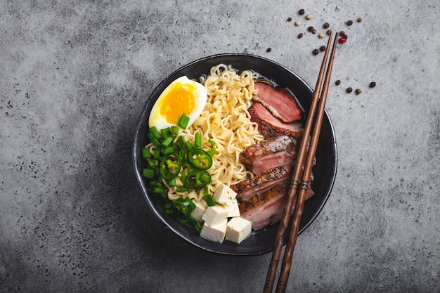 Deliziosa zuppa di noodle asiatici ramen in una ciotola con brodo di carne, tofu, fette di maiale, uova con tuorlo, fondo di cemento rustico grigio, primo piano, vista dall'alto. zuppa calda e gustosa di ramen giapponese per cena in stile asiatico