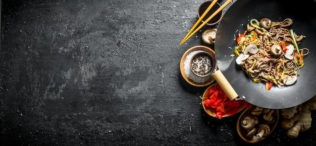 Tagliatelle asiatiche deliziose di soba con spezie, funghi e zenzero sulla tavola di legno nera