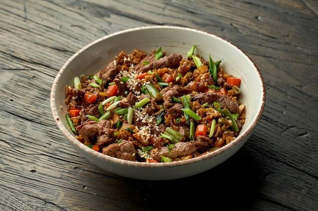 Delizioso cibo asiatico di strada - riso wok con carne di manzo, cipolle verdi, verdure e semi di sesamo in una ciotola bianca su una superficie di legno