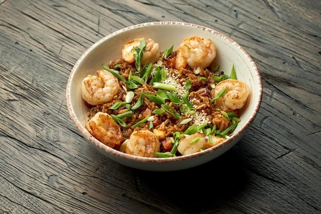 Delizioso cibo asiatico di strada - riso wok con gamberetti, cipolle verdi, verdure e semi di sesamo in una ciotola bianca su una superficie di legno