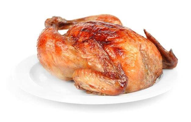 Delizioso pollo al forno su piatto isolato su bianco
