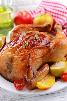 Delizioso pollo al forno sul piatto sul primo piano del tavolo