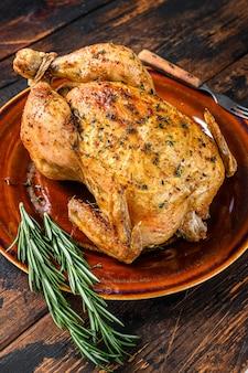 Pollo al forno delizioso sulla tavola di legno. sfondo scuro. vista dall'alto.