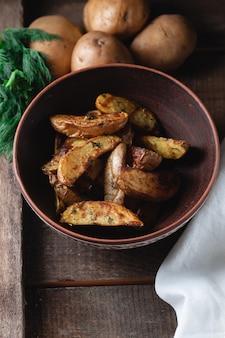Deliziose patate al forno del paese in una ciotola di terracotta con spezie, aneto e cipolle verdi su un tavolo di legno, vista dall'alto
