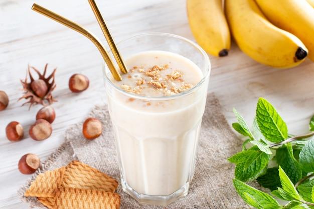 Delizioso frullato di banana con banane a fette e biscotti in vetro su sfondo bianco. colazione salutare.