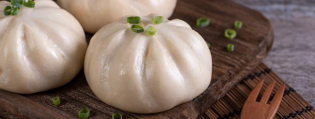 Delizioso baozi, panino di carne al vapore cinese è pronto da mangiare sul piatto da portata e sul piroscafo, primo piano, copia spazio concetto di design del prodotto.