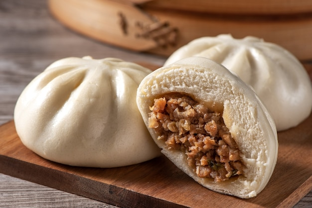 Delizioso baozi, panino di carne al vapore cinese è pronto da mangiare sul piatto da portata e sul piroscafo, da vicino, copia spazio concetto di design del prodotto.
