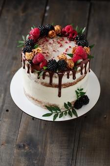 Torta fatta a mano deliziosa e bella. pasticceria per le feste. dessert decorato con frutti di bosco freschi, foglie verdi e dolci.