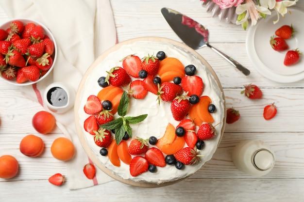 Deliziosa torta di crema di bacche sulla tavola di legno bianco