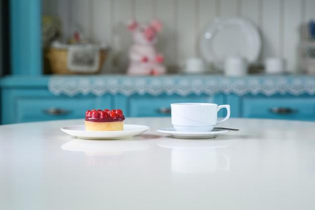 Delizioso tè ai frutti di bosco e tarte con lamponi su un tavolo in un'accogliente caffetteria