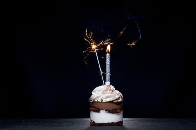 Candela deliziosa del fuoco d'artificio del bigné di compleanno sulla tavola contro il buio