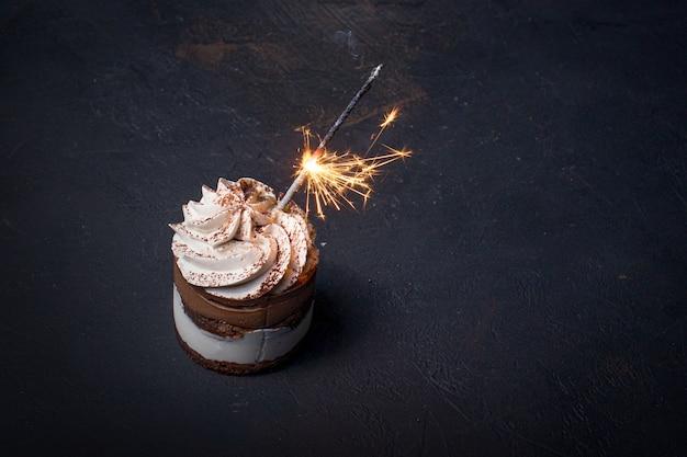 Bigné delizioso di compleanno con la candela del fuoco d'artificio sul tavolo su sfondo scuro