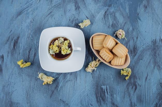 Deliziosi biscotti con una tazza di tisana sulla superficie blu.