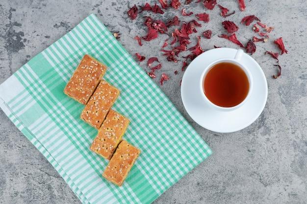 Deliziosi biscotti con semi di sesamo e tazza di tè aromatico sulla superficie in marmo.