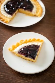 Deliziosa torta di formaggio ai mirtilli su piatto bianco Foto Premium