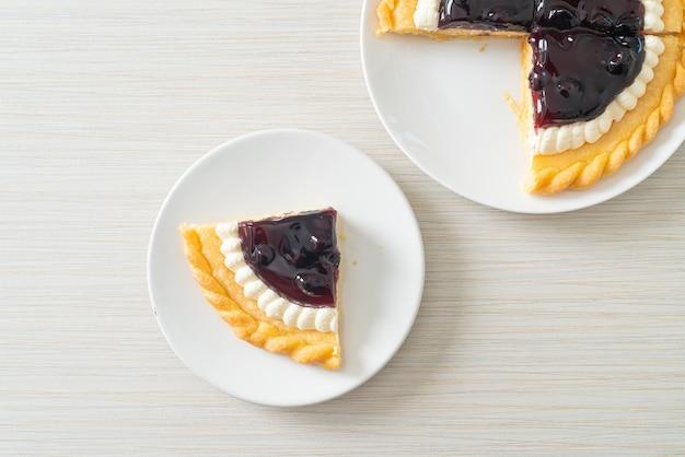 Deliziosa torta di formaggio ai mirtilli su piatto bianco