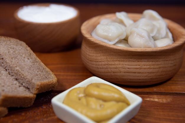 Deliziosi gnocchi bolliti su uno sfondo di legno con salsa di senape, panna acida e pane. Foto Premium