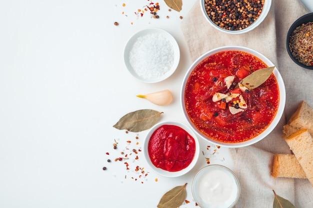 Delizioso borscht con aglio e alloro su uno sfondo bianco. vista laterale con copia spazio.