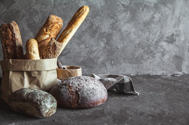 Merce nel carrello del pane delizioso sulla tavola di legno su fondo grigio