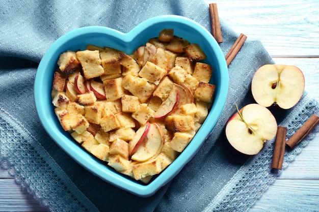 Budino di pane delizioso con mele in ciotola a forma di cuore sul tovagliolo