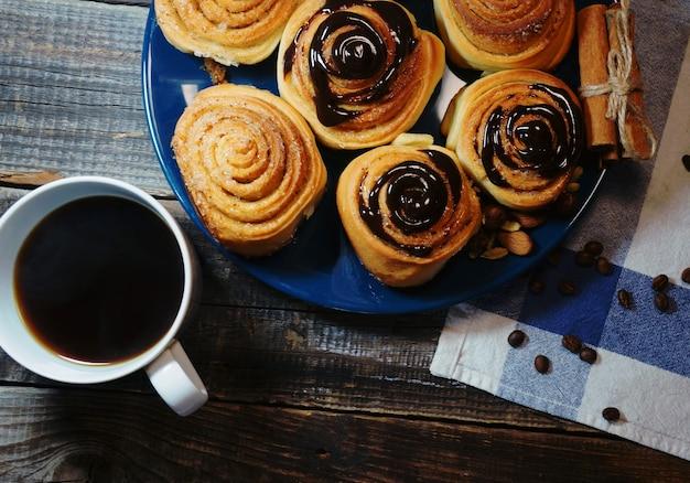Deliziosa colazione, panino alla cannella ricoperto di cioccolato e una tazza di caffè