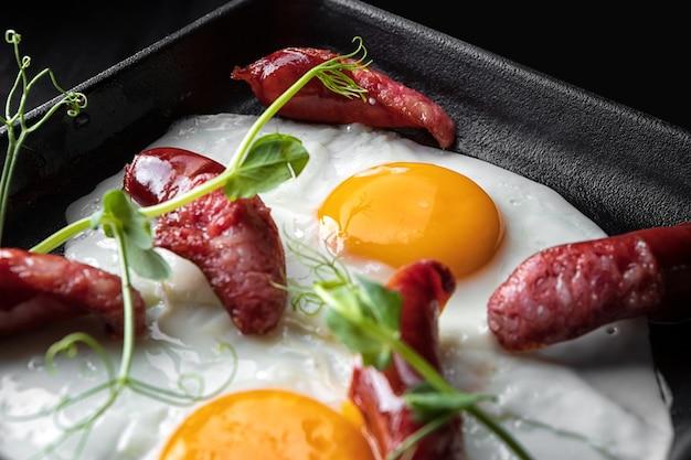 Deliziosa colazione, uova fritte con salsicce e germogli di piselli, su una padella nera