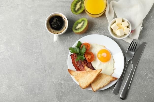 Prima colazione o pranzo deliziosa con le uova fritte su superficie grigia, vista superiore