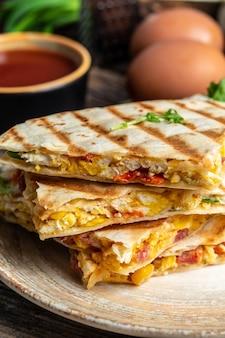 Deliziose tortillas di quesadilla per la colazione con uova strapazzate, verdure, prosciutto e formaggio. immagine verticale