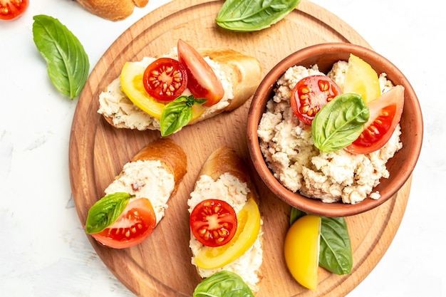 Deliziosa colazione o spuntino gustoso panino con pomodori, crema di formaggio e foglie di basilico su sfondo bianco, cibo pulito, dieta, concetto di cibo vegano. vista dall'alto.
