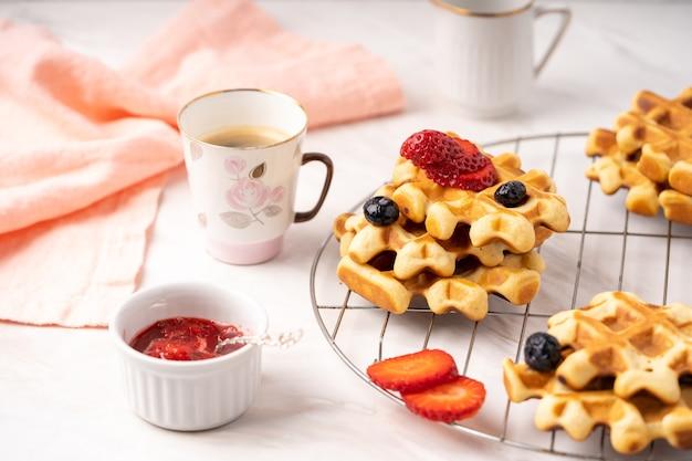 Delizioso tavolo per la colazione, cialde con frutti di bosco, marmellata e tazza di caffè.