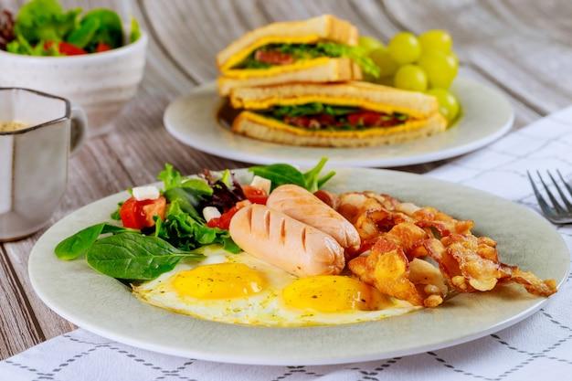 Deliziosa colazione con uova, salsicce, pancetta e tazza di caffè.