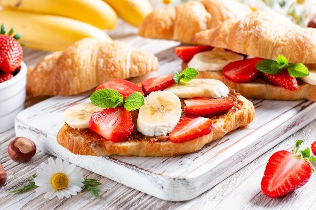 Deliziosa colazione con croissant freschi, banana e fragola sul tavolo di legno wooden