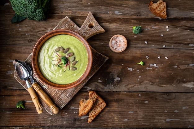 Deliziosa zuppa di crema di broccoli servita con microgreen, semi di zucca
