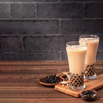 Delizioso tè al latte con bolle di tapioca perla palla in vetro sulla tavola di legno