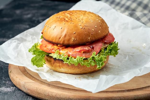 Hamburger delizioso con pollo, pomodori, lattuga, formaggio fuso al cetriolo su pergamena bianca. superficie scura. fast food americano. hamburger di pollo