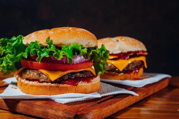 Deliziosi hamburger con pancetta e formaggio cheddar e con lattuga, pomodoro e cipolla rossa e pancetta e cheddar su pane fatto in casa con semi e ketchup su una superficie di legno e sfondo nero.