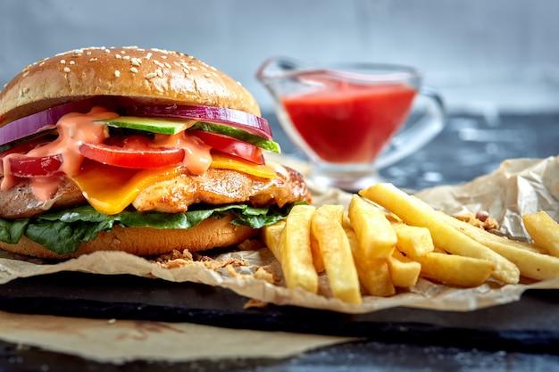 Deliziosi hamburger con carne di manzo, formaggio al pomodoro e patatine fritte con salsa di pomodoro
