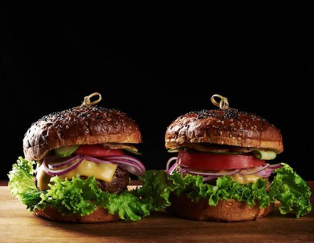 Deliziosi hamburger con cotoletta di manzo fritta, pomodoro, lattuga e cipolle, panino croccante di farina di grano bianco con semi di sesamo. fast food su una tavola di legno