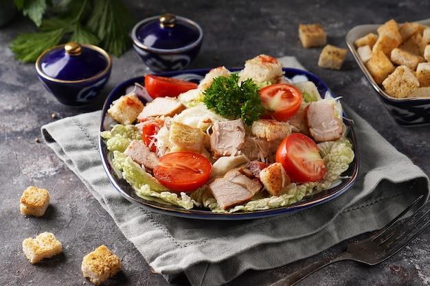 Deliziosa insalata caesar con pollo, cavolo, uova e pane tostato servito nel piatto